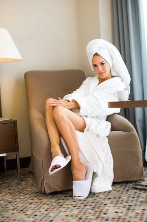 Young adult beautiful woman in hotel suit sitting in comfortable armchair with cup of tea in morning. the towel is tied on the head Stock Photo