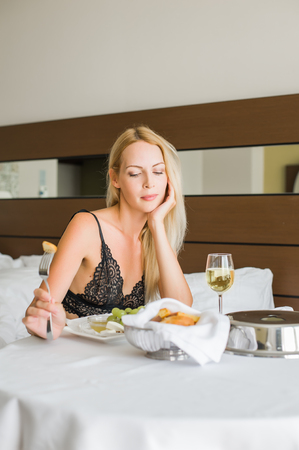 Young beautiful blond woman having lunch in hotel room on vacations and holding fork with a cheese Stock Photo