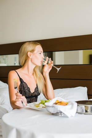 Young beautiful blond woman having lunch in hotel room on vacations and drink white wine from glass