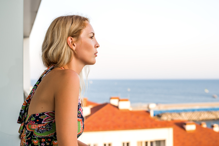 Beautiful woman Looks at the sea from the buildings balkon. Visible roofs of neighboring buildings.