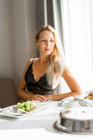 Young beautiful blond woman having lunch in hotel room on vacations