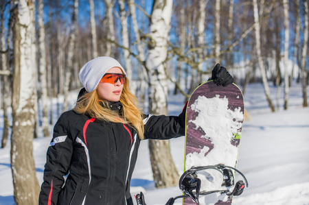 Young adult woman snowboarder holding board in heand in snow winter Stock Photo