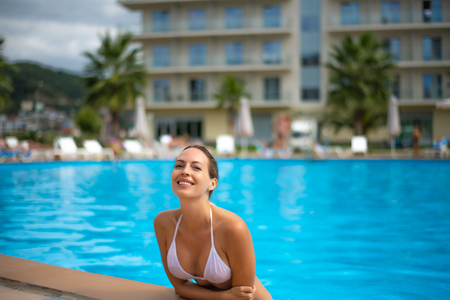 Beautiful young adult smiling woman in outdoor waterpool in resort hotel Stock Photo