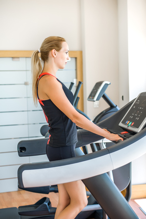 Young beautiful woman with slim sporty figure is engaged on a treadmill in the gym Stock Photo