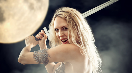 beautiful sexy warrior viking girl with a sword in hands attack and screaming outside in light of full mun in midnight Stock Photo