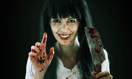 Halloween horror. Crazy bloody scary smiling maniac girl holding knife butcher cleaver pointing at you into camera on black background