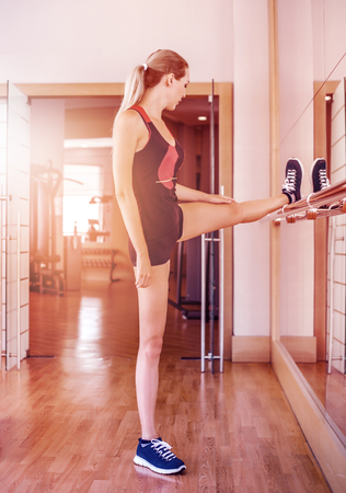 Beautiful slim girl engaged in fitness in the gym, doing stretching at the mirror bar in class