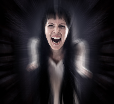 Halloween horror. Crazy bloody scary zombie woman looks into the camera and screams on black background