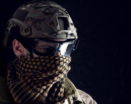 Nahaufnahmeporträt des gutaussehenden Militärs. Makroaufnahme auf schwarzem Hintergrund beim Betrachten der Kamera