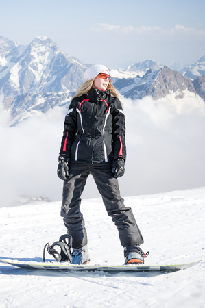 Young adult woman snowboarder standing on a snowboard one foot in the clasp of the other in the snow in winter on the mountainside Stok Fotoğraf
