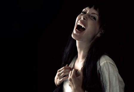 Halloween horror. Crazy bloody scary vampire girl with fangs screaming on black background