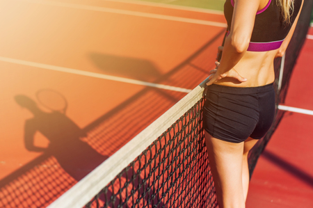 Young beautiful Woman holding racket stay back on tennis court during match