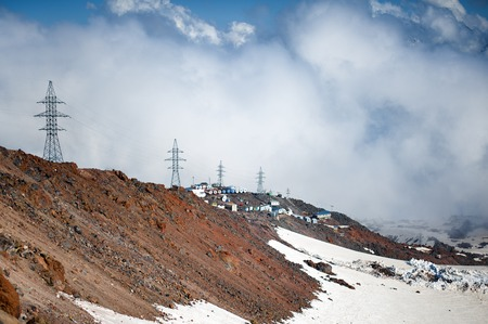Clubs of fog and clouds move along the slope of Mount Elbrus