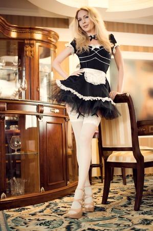 Seksowna pokojówka Młoda piękna dziewczyna w krótkiej bujnej czarnej sukience z fartuchem i białymi nylonowymi pończochami Zdjęcie Seryjne
