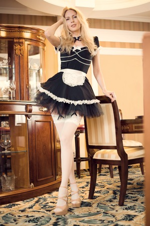 Focus on face. Sexy maid Young beautiful girl in a short lush black dress with an apron and white nylon stockings