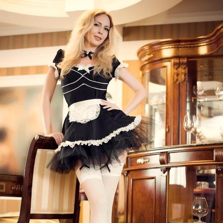 Seksowna pokojówka Młoda piękna dziewczyna w krótkiej bujnej czarnej sukience z fartuchem i białymi nylonowymi pończochami