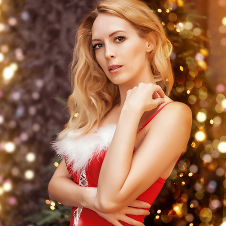 Beautiful blond sexy woman in red christmas dress with white fur on breast stay near christmas eve with lights and decorations. Portrait