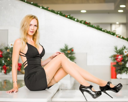 Young beautiful blond girl with long slim legs in short black dress