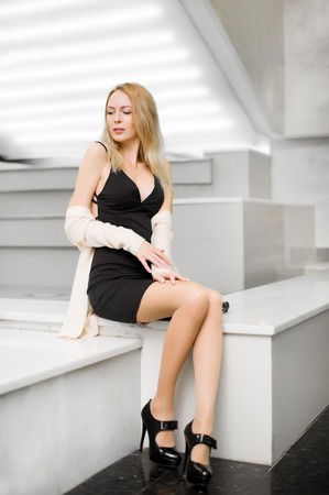 Young beautiful blond girl with long slim legs in sexy short black dress