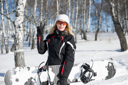 Young adult woman snowboarder holding board in hand in snow winter in sportswear smiles and shows two fingers