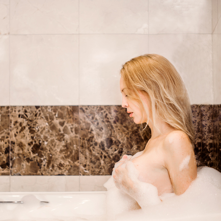 Young beautiful blonde qirl in the suds is in the bathroom Stock Photo