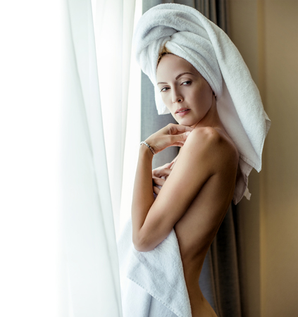 Amazing and beautiful sexy young woman hair wrapped in a towel standing by the window
