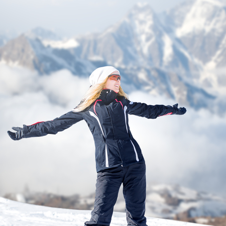 Young adult woman snowboarder or skyier in winter sportswear in the snow stay on the mountainside. Happiness with hands to the side