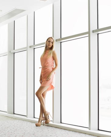 Beautiful young stylish woman near the window in the office building