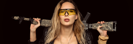 Sexy blond dangerous woman with automatic rifle wearing Leather Jacket and yellow glasses on black background Stock Photo