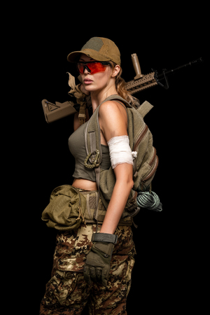 Dangerous military girl holding automatic rifle. Dooms day or war on black