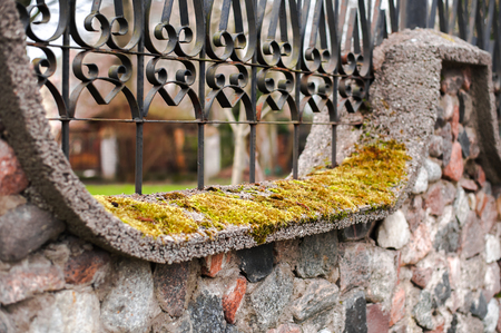 close up - stone fence with wrought-iron fence and moss