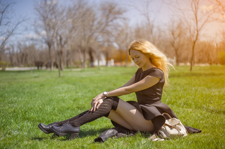 Young fashionable girl with long blond hair, black dress and stockings sitting on spring grass in sunny day