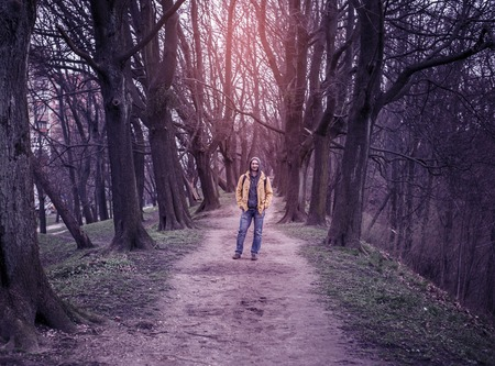 The trodden path in a mysterious mystical place among the tall old trees and young man in hoody jacket