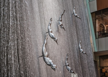Waterfall and sculptural composition of pearl divers or falling, flying people in the Dubai Mall
