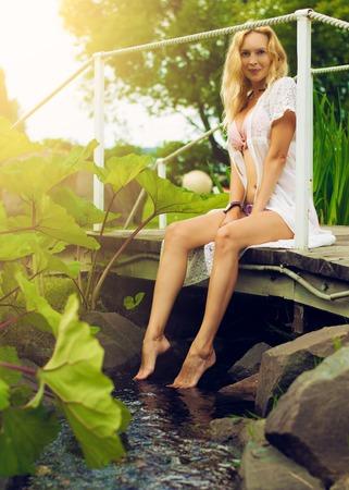 Youmg beautiful blond woman in beautiful summer garden