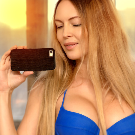 A beautiful girl with long light brown hair holds a mobile phone in a dark brown wooden case