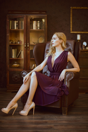 Sexy young woman in a purple dress sits in a large vintage leather chair for the head in an expensive luxury dark interior in high-heeled shoes. 版權商用圖片
