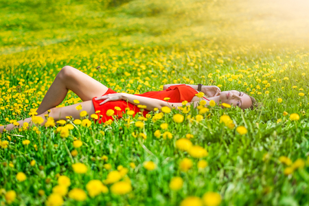 Beautiful happy slim young female student in a bright red dress cuts in the middle of a green field or meadow in yellow dandelions
