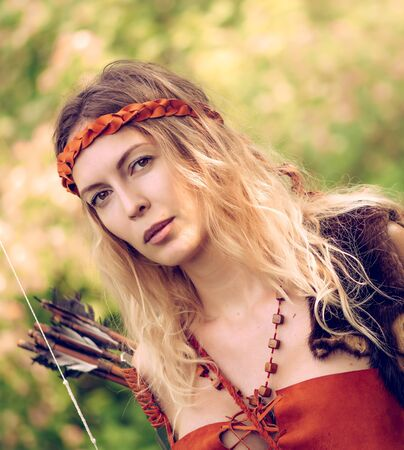 Beautiful girl archer with long blond hair with a bow and arrows dressed in leather and wristwear looking at camera Фото со стока
