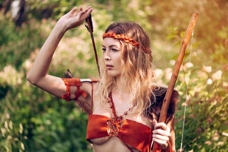 Beautiful girl archer with long blond hair with a bow and arrows dressed in leather and wristwear pulls an arrow out of the quiver