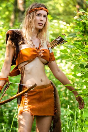 Beautiful girl archer with long blond hair with a bow and arrows dressed in leather and wristwear