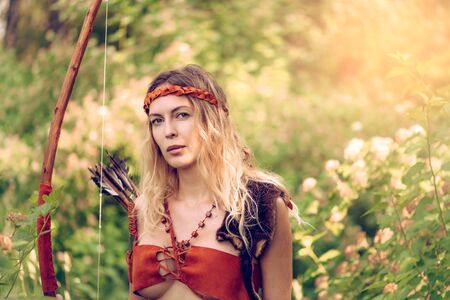 Beautiful girl archer with long blond hair with a bow and arrows dressed in leather and wristwear looking at camera Stock Photo