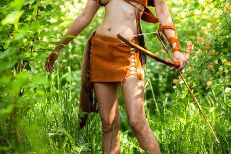 Foto recortada de hermosa arquera con arco y flechas vestida con cuero y muñequera
