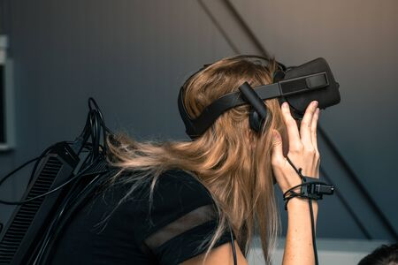 Virtual reality with full immersion. The girl is wearing virtual reality glasses on her head