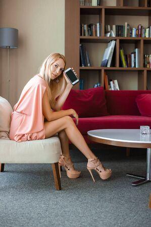 Mooie slanke blonde meid in een modieuze roze zomerjurk op hoge hakken zit op de bank en houdt de telefoon vast