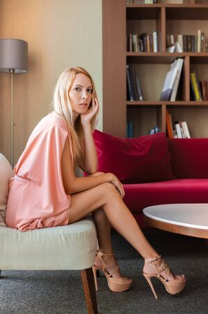 Beautiful slim girl blonde in a fashionable pink summer dress in high heels sits on a chair in a beautiful living room and looks into the camera