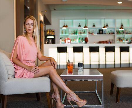 Rubia hermosa chica delgada en un vestido de verano rosa de moda en tacones altos se sienta en una silla en un hermoso bar de moda
