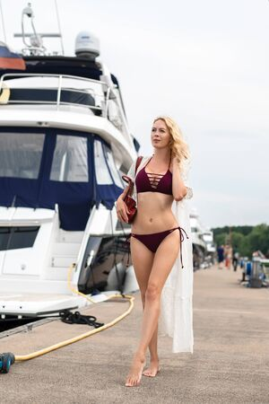 Beautiful sexy girl with a slim figure is standing on a wooden pier in a yacht club near motor yachts