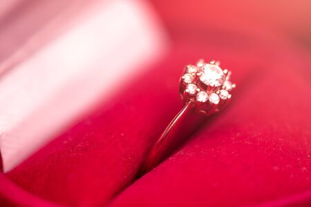 Defocus texture Valentines Day background with diamond engagement ring into a red heart box Imagens