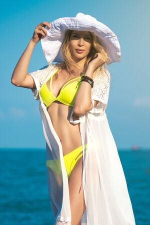Portrait of gorgeous girl model on the beach on seaside wearing yellow swimsuit, white dress or robe with lace and big round hat